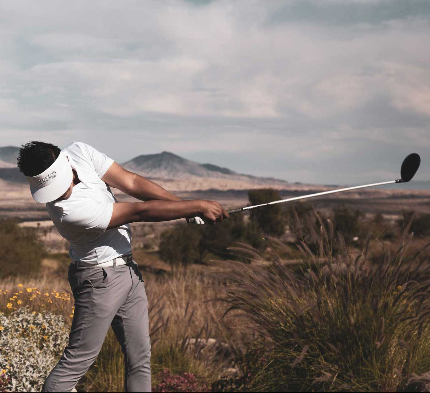Golfer mid swing at Rams Hill Golf Course with the Anza Borrego Desert in the background