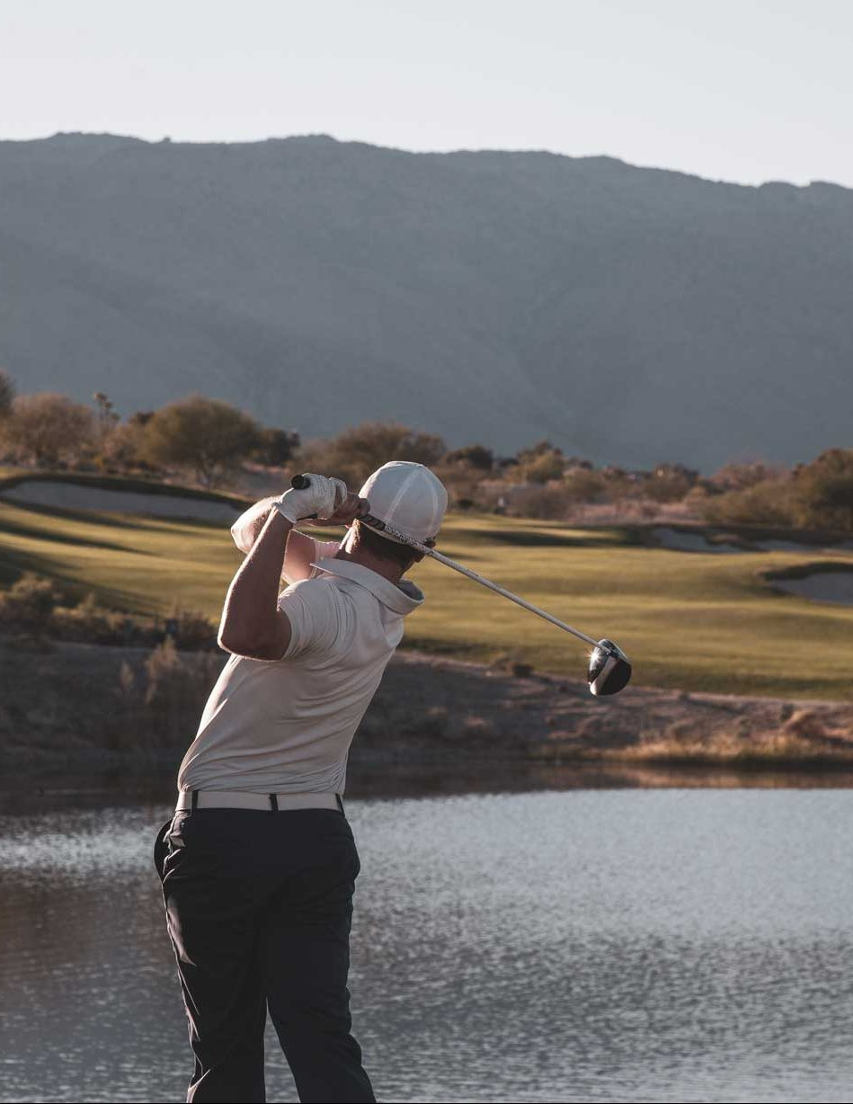 Back of golfer finishes his swing above a pond at Rams Hill Golf Club