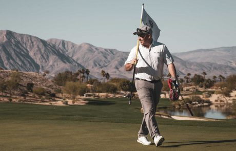 Golfer walks around Rams Hill golf course carrying a flag with the Santa Rosa mountains in the background