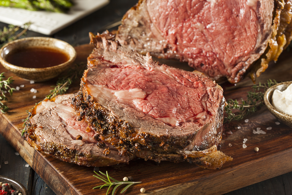 Slices of prime rib grilled medium on cutting board for Rams Hill Season Opener