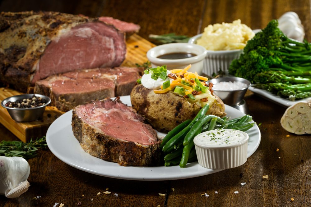 Prime rib dinner with potatoes and seasonal vegetables on wood table for Rams Hill Season Opening