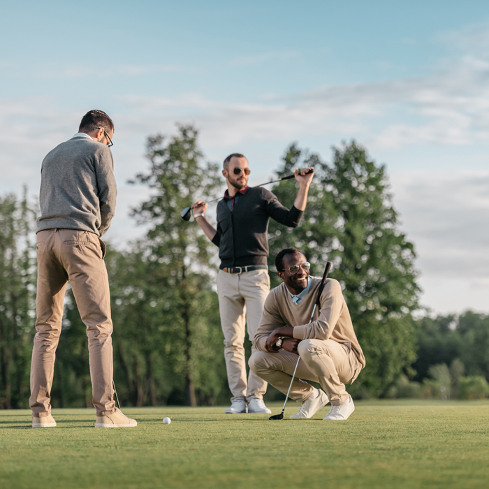 multiethnic stylish wearing winter golf clothes laughing and putting on golf course