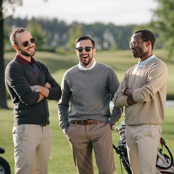 multiethnic men wearing stylish golf winter clothes speaking together on golf course