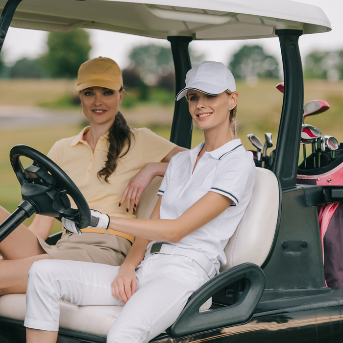 two stylish women wearing fall golf attire in a golf cart on a golf course