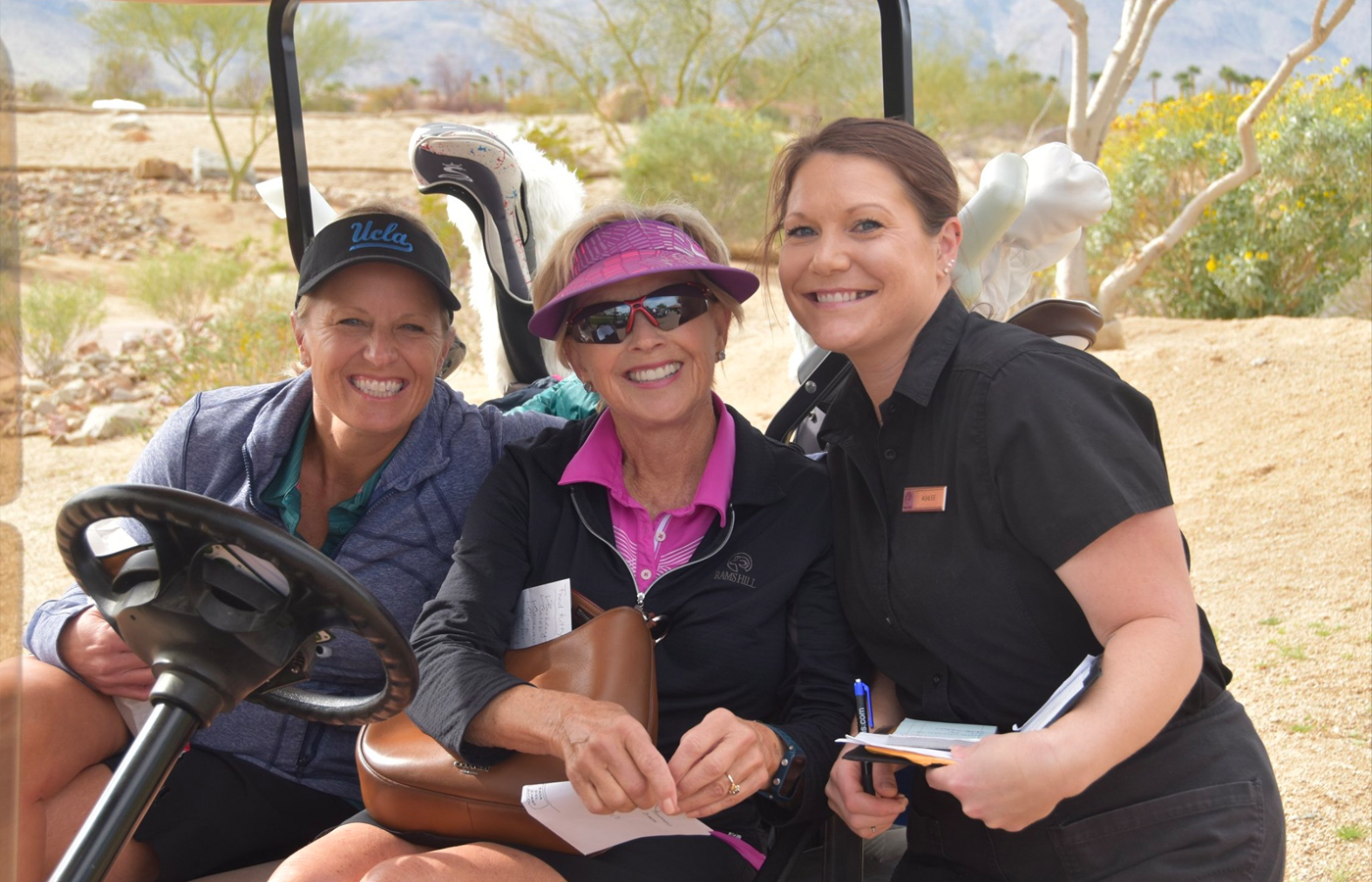 female rams hill employees on golf cart smiling on course